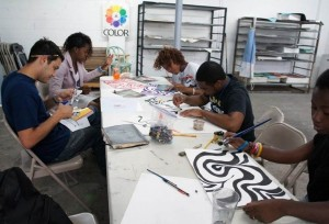Teaching Artist Carlos Noguera (far left) works on a design project with the ArtWorks interns.